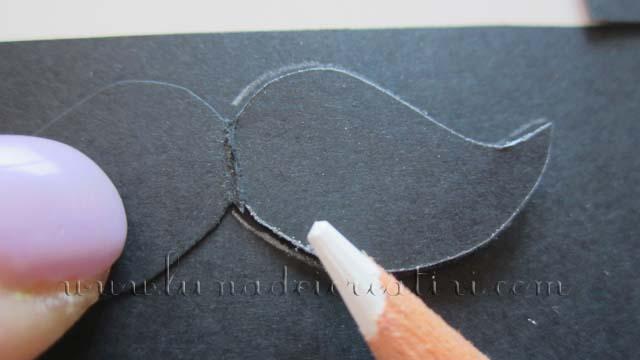 Appoggia i baffi ottenuti sul cartoncino nero e con la matita bianca tracciane il contorno